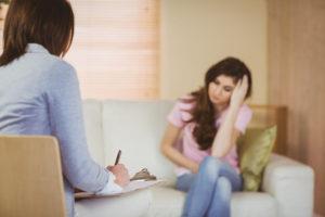 Psicóloga hablando y paciente oyendo.